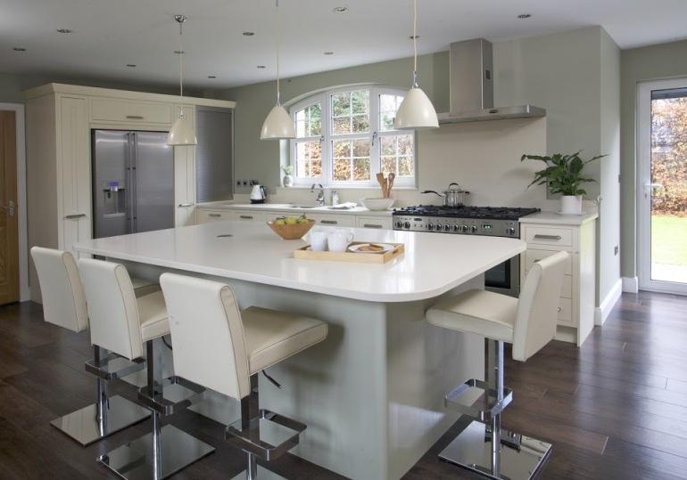 beautiful-kitchens_white-leather-bar-stool-white-gloss-kitchen-chimney_white-granite-countertops_double-pendant-lamp_glass-kitchen-windows_texture-wooden-kitchen-flooring.jpg